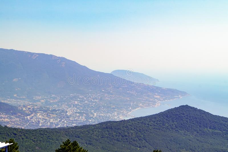 View from the peak of Mount Ai-Petri on the slopes of the mountains and the Black Sea coast. Crimea stock photos