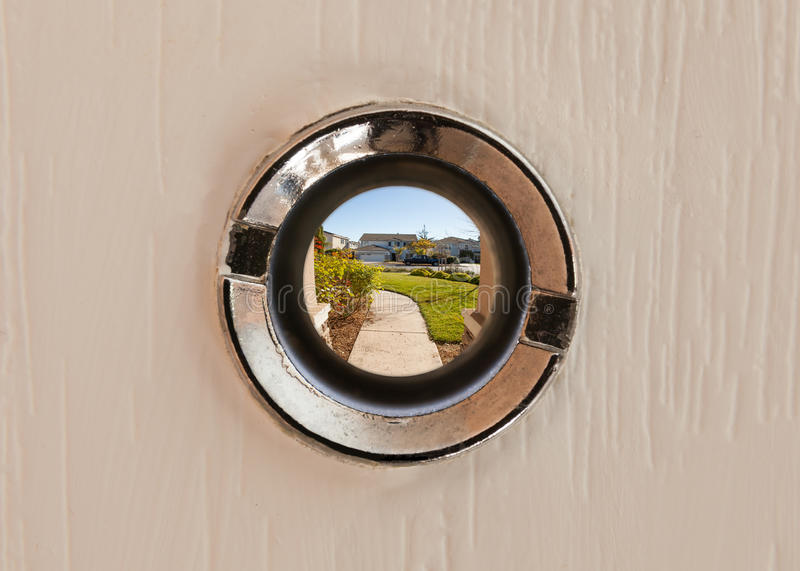 View through the peephole. A view through the peephole onto the street in suburbia stock photo