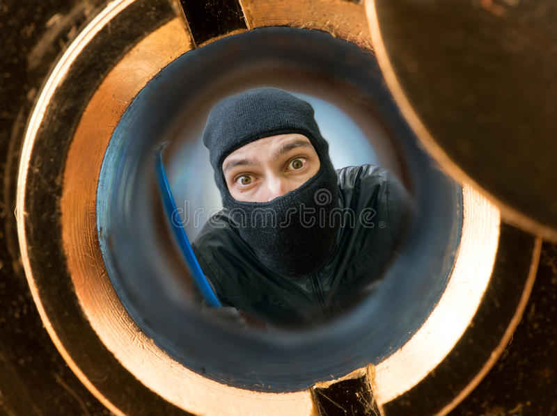 View through peephole. Robber or burglar masked with balaclava behind door. View through peephole. Robber or burglar masked with balaclava behind the door stock image