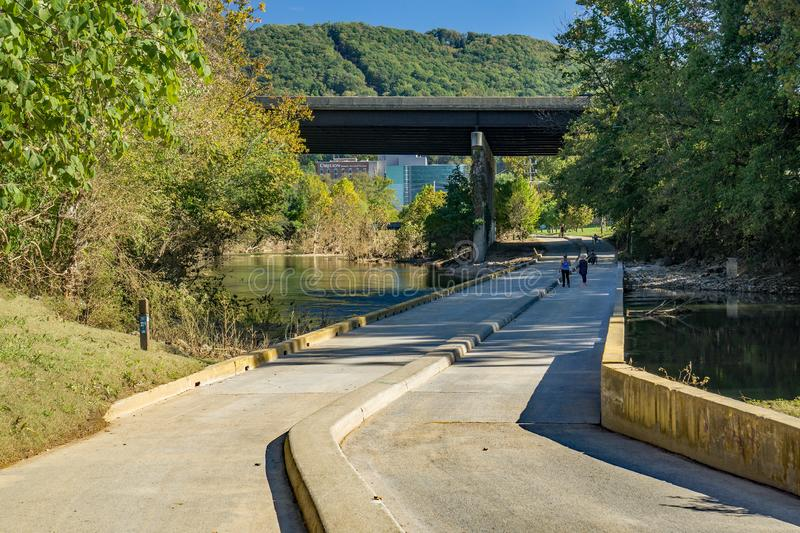 View of People Crossing the Smith Park Low Water Bridge. Roanoke, VA – OCT 19th: Early morning walkers crossing the Smith Park low water bridge on the royalty free stock photos