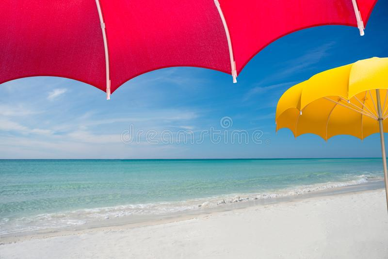 View of perfect pristine beach from under bright red umbrella. View of perfect untouched pristine white sand blue water beach with wispy cirrus clouds from under royalty free stock image