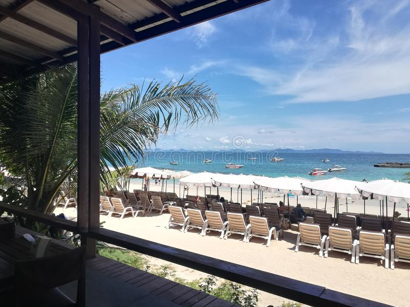 View a perfect white sand beach with line of sun beds in Pattaya Thailand, aquamarine ocean and blue sky on background royalty free stock image