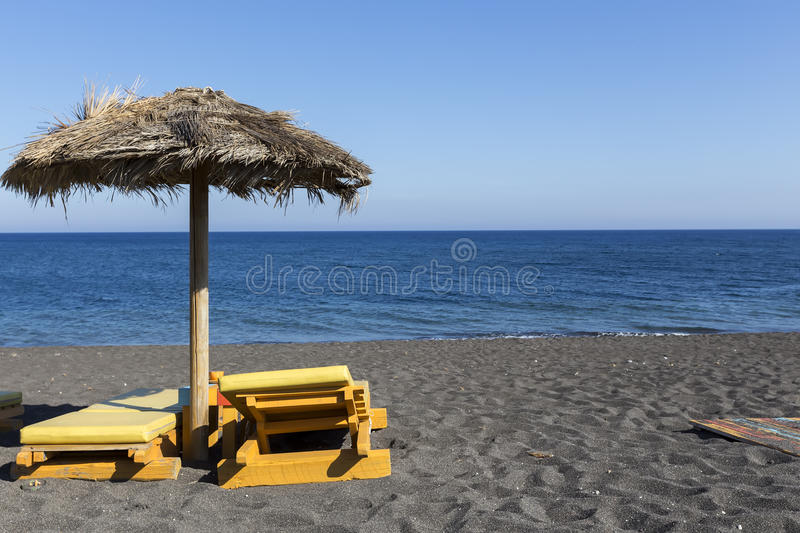view of Perissa beach on the Greek island of Santorini with sunbeds and umbrellas. Beach is covered with fine black sand, and royalty free stock image