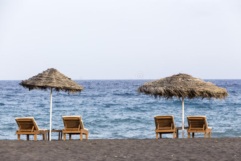 view of Perissa beach on the Greek island of Santorini with sunbeds and umbrellas. Beach is covered with fine black sand, and royalty free stock photo