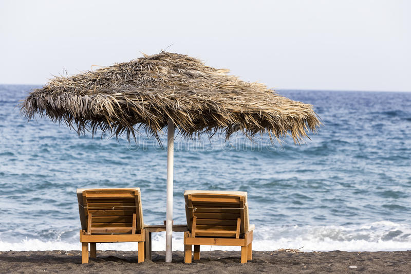 view of Perissa beach on the Greek island of Santorini with sunbeds and umbrellas. Beach is covered with fine black sand, and royalty free stock photos
