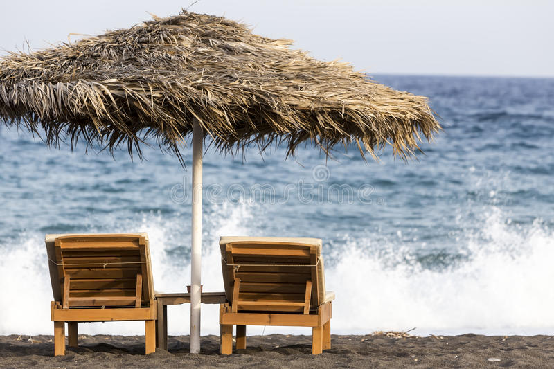 view of Perissa beach on the Greek island of Santorini with sunbeds and umbrellas. Beach is covered with fine black sand, and stock photography