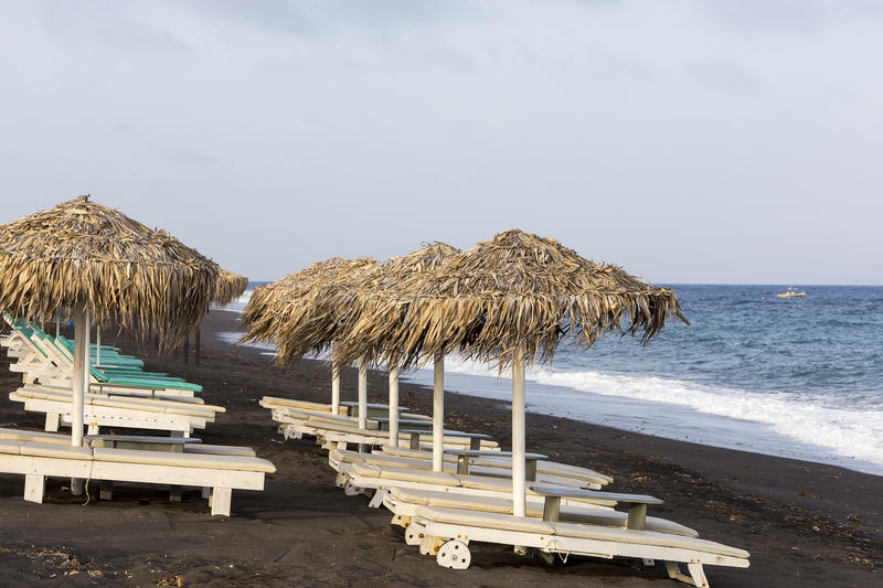 view of Perissa beach on the Greek island of Santorini with sunbeds and umbrellas. Beach is covered with fine black sand, and royalty free stock photography
