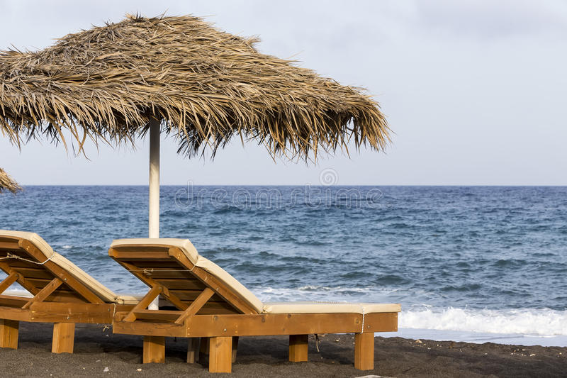 view of Perissa beach on the Greek island of Santorini with sunbeds and umbrellas. Beach is covered with fine black sand, and stock images