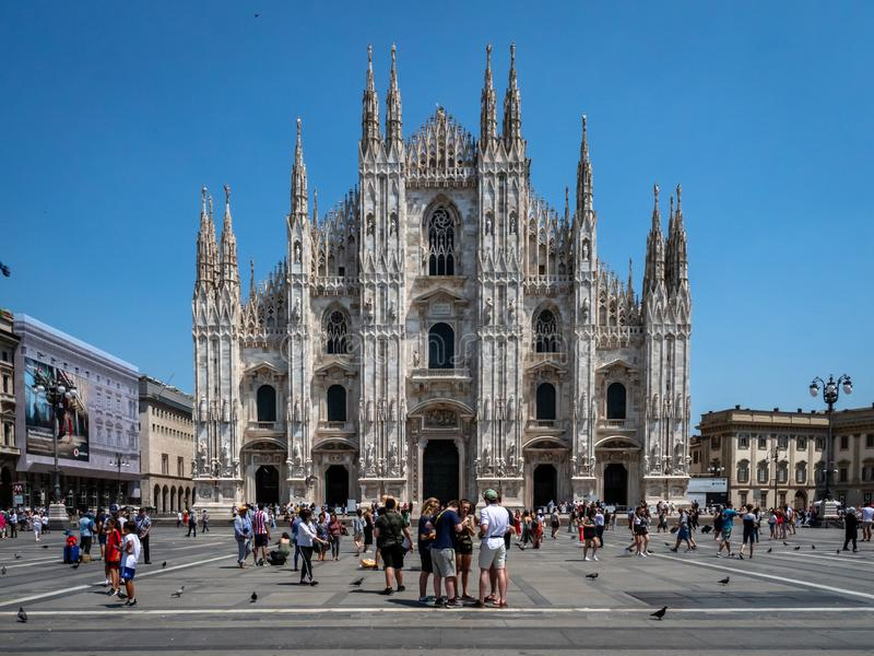 View of the Piazza del duomo with tourists visiting the famous cathedral the Milano Duomo. Milan, Italy - June 30, 2019: View of the Piazza del duomo with stock photos