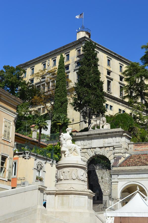 View from Piazza della Liberta, Udine, Italy. Udine Castle, Loggia di San Giovanni,  monument of peace and the Palladian Arco Bollani all viewed on a sunny day royalty free stock images