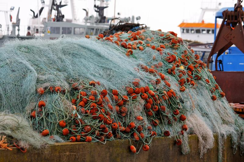 Pile of fishing net. View of a pile of fishing net with plastic floaters, with boats on the background stock photography