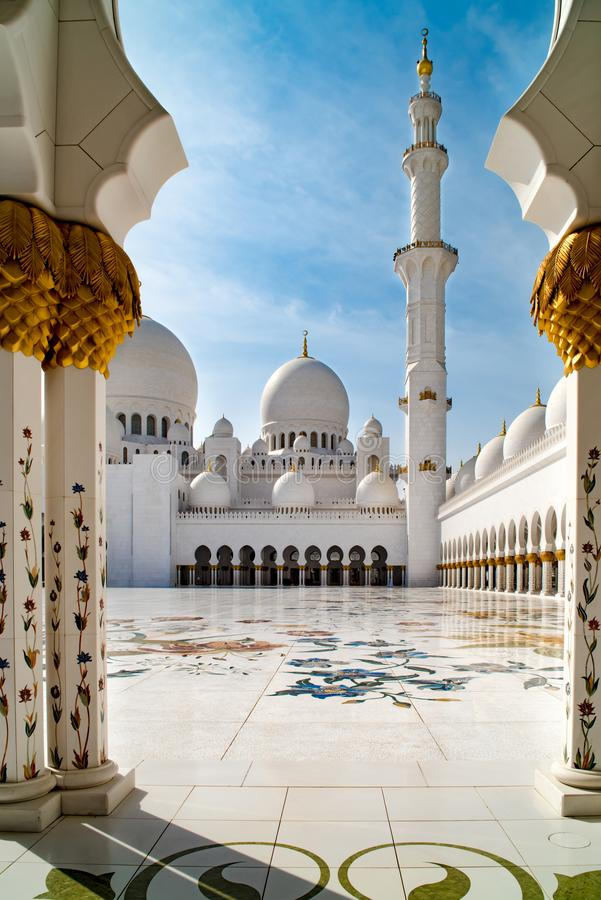 View through pillars to flowers and arabesques on floor and domes of Grand Mosque Abu Dhabi, UAE stock photo