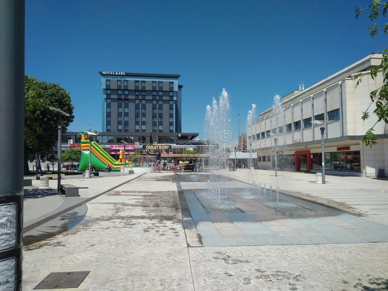 View of central square with fontaine in Pirot, Serbia. View pirot serbia street fountain working sunny day blue sky water summer central square fontaine hotel stock images