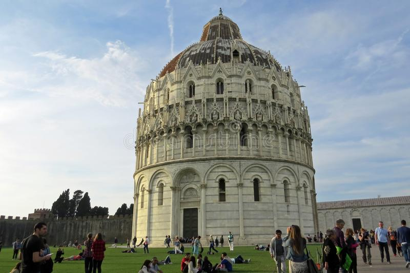 View on the Pisa Baptistery of St. John Battistero di San Giovanni and on people relaxing in front of it; Piazza des Miracoli; P. The Pisa Baptistery of St. John royalty free stock images