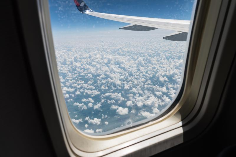 View from the plane`s porthole on the plane`s wing, the ground below and the clouds of a summer day in flight. Here is view from the plane`s porthole on the stock photos