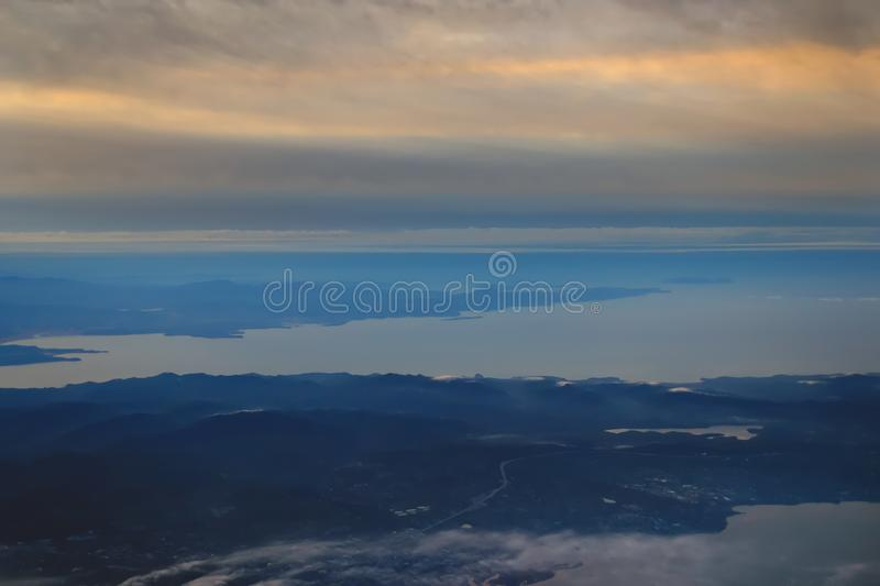 View from the plane to the island of Sakhalin, the mountains and the sea with the seaport royalty free stock photography