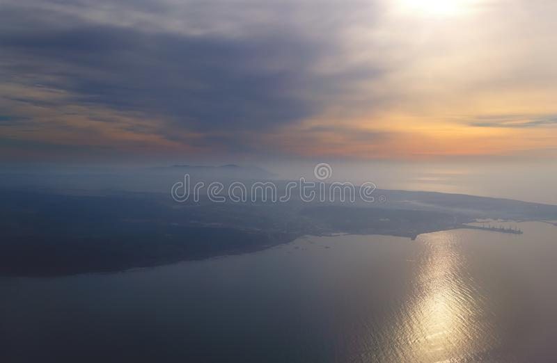 View from the plane to the island of Sakhalin, the mountains and the sea with the seaport. stock image