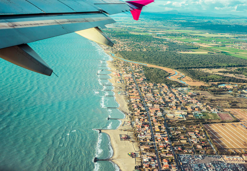 View from the plane. On the wing sea and land stock image