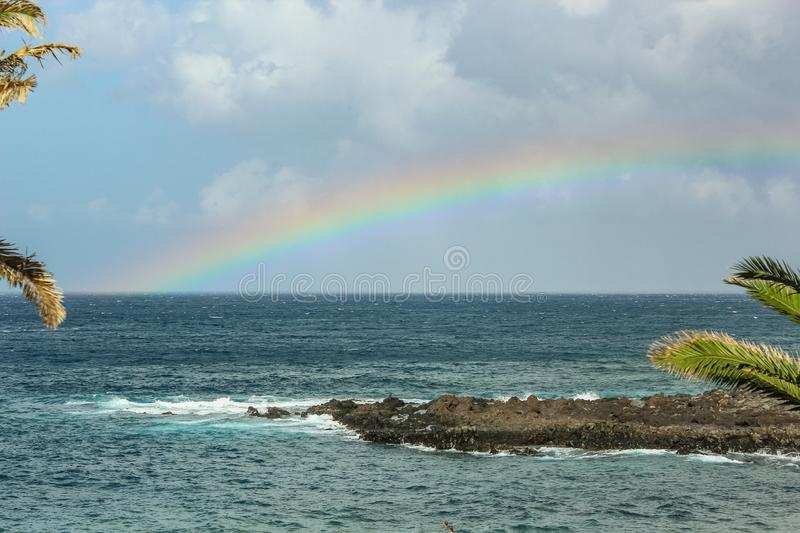 View of the Playa de la Arena and rainbow over the sea, the phenomenon of nature, bright colors on the rainbow and cloudy sky stock photography