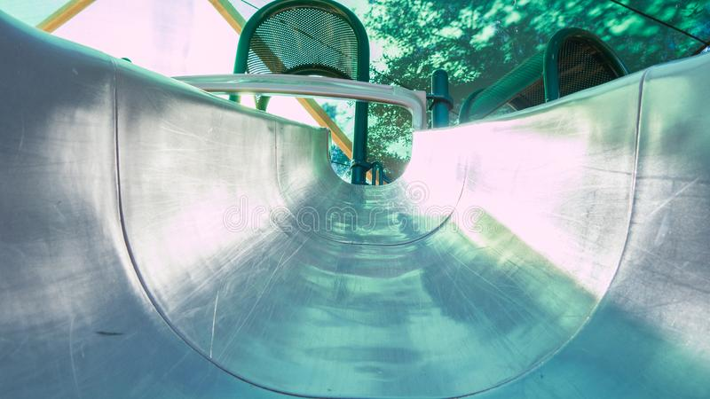 View of a playground slide, looking up to the top from the bottom of the slide stock image