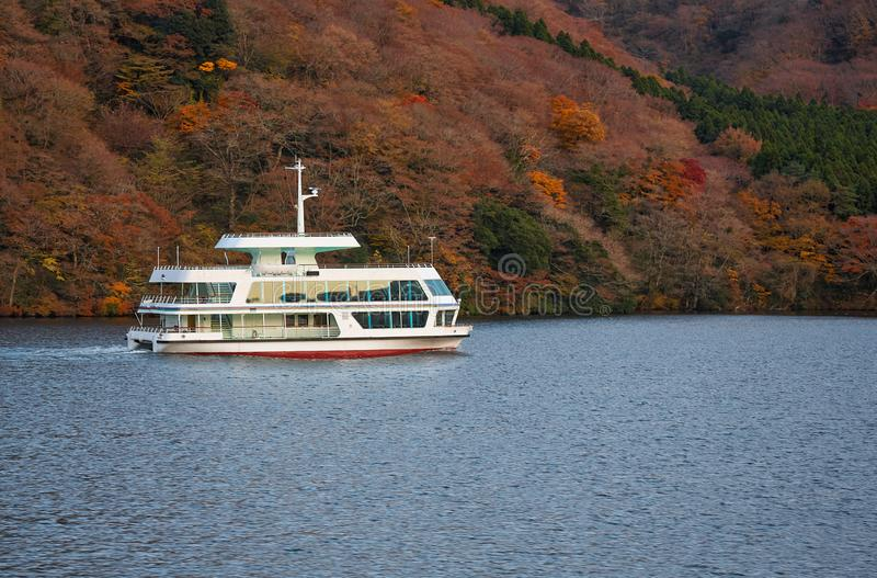 Pleasure boats  on Lake Ashi. Hakone, Kanagawa. Honshu. Japan. The view of pleasure boat on Lake Ashi with the lake shore covered with the autumn foliage on the stock photo