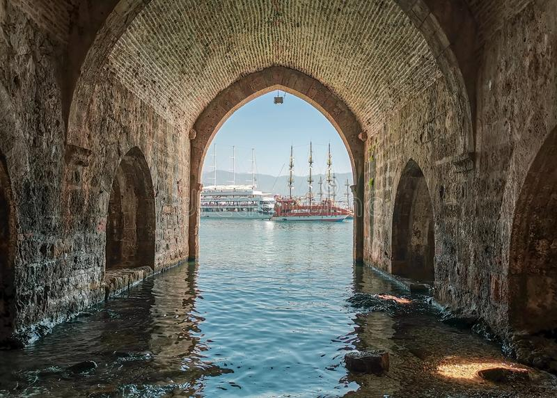 View of pleasure tourist yachts through the stone arch of an old shipyard in Turkish Alanya. In the afternoon stock photography