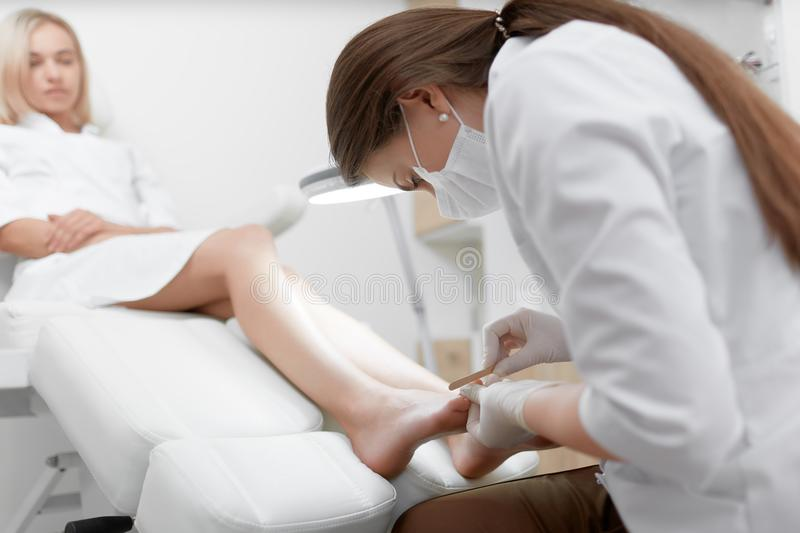 Podiatrist doctor in white making polish procedure for foot. stock image