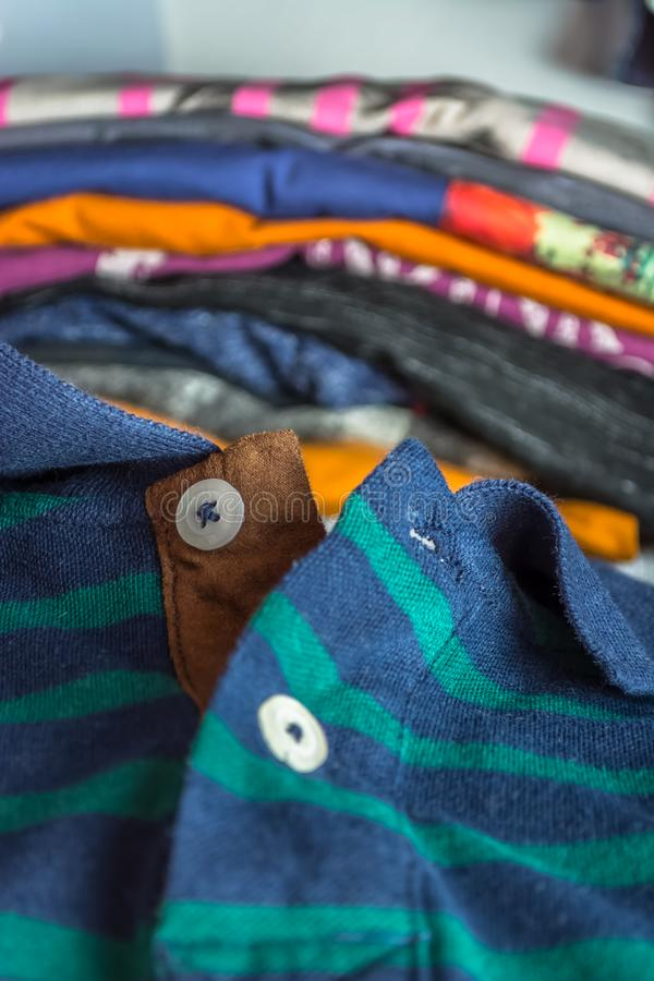 View of a polo shirt, casual green and blue colors. With colored t-shirts as background set adult front sale pattern beauty textile light quality cotton texture royalty free stock photography