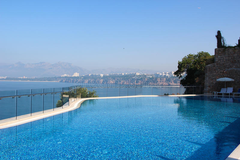 A view of the pool and the sea with turquoise clear water with a mountain range on the horizon and the line of the Mediterranean. Coast with the resort town in stock photography