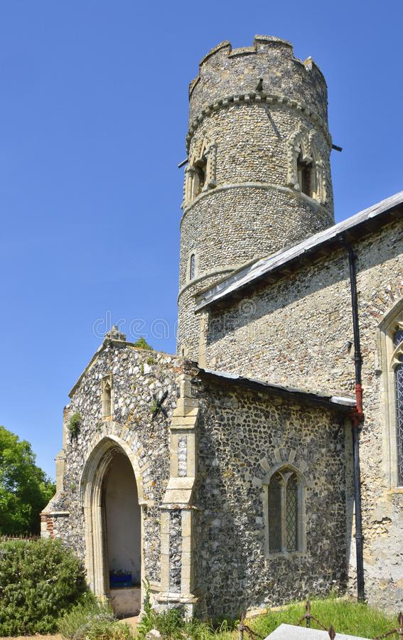 Historic Church Tower of East Anglia. View of the porch and c. 11th century tower sections, showing c. 15th century chequered battlemented parapet top, of the stock photos