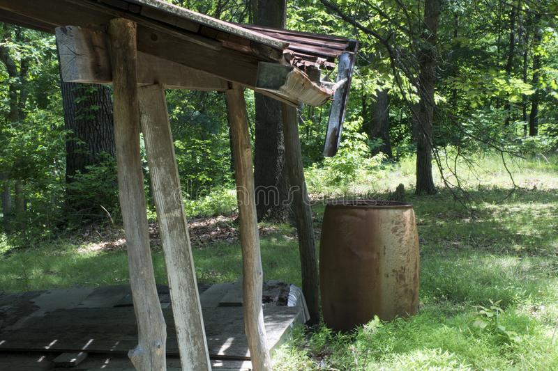 Porch and rain barrel overlooking a forest. A view from the porch shows the rain barrel at the corner, posts made of cut trees form the supports for the roof.the royalty free stock photos