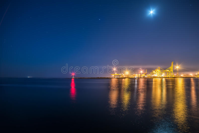 A view of the port facilities,. A small lighthouse at the entrance to the port. Night photo royalty free stock photos