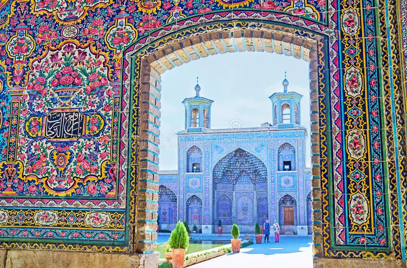 In old mosque of Shiraz, Iran. The view on the portal of Nasir Ol-Molk mosque with two small minarets and muqarnas decoration, Shiraz, Iran stock image