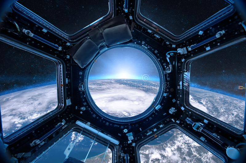 View from a porthole of space station on the Earth background. royalty free stock image
