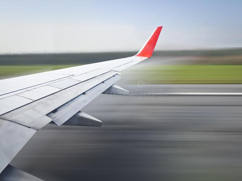 View from the porthole - Wing of an airplane taking off above the runway at high speed royalty free stock images