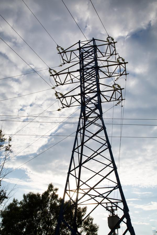 View of the power line against the clouds of blue sky in the sunlight. royalty free stock photo