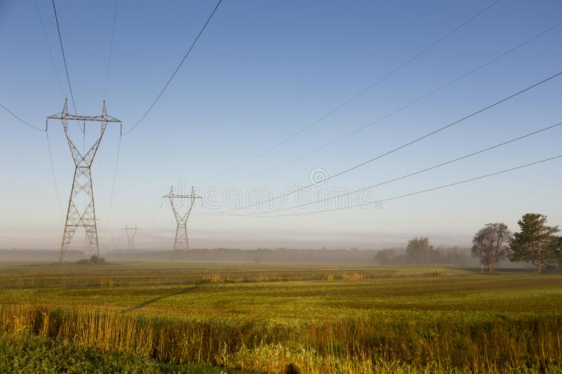 View of power line towers in farmland fields during a beautiful misty late summer golden hour morning. St.-Charles-de-Bellechasse, Quebec, Canada royalty free stock photography