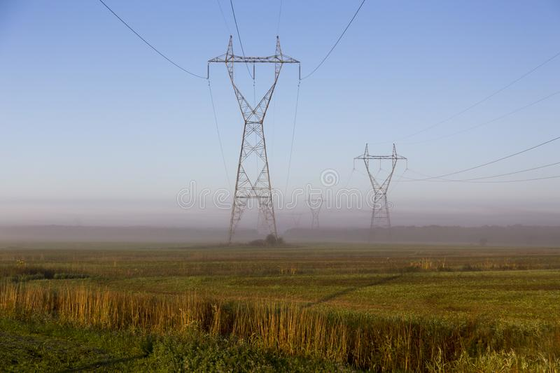 View of power line towers in fields during a beautiful misty late summer golden hour morning. St.-Charles-de-Bellechasse, Quebec, Canada stock photo