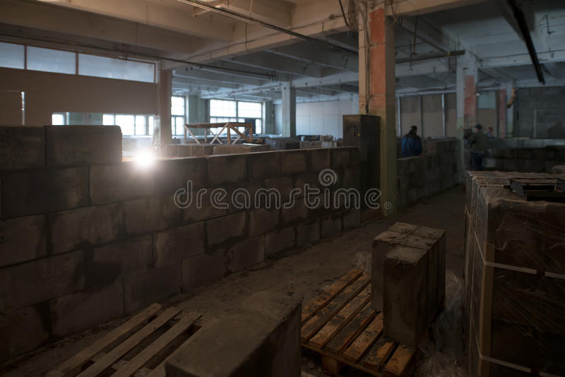 View of a premise being repaired. With builders working and walls of aerated concrete in construction stock image