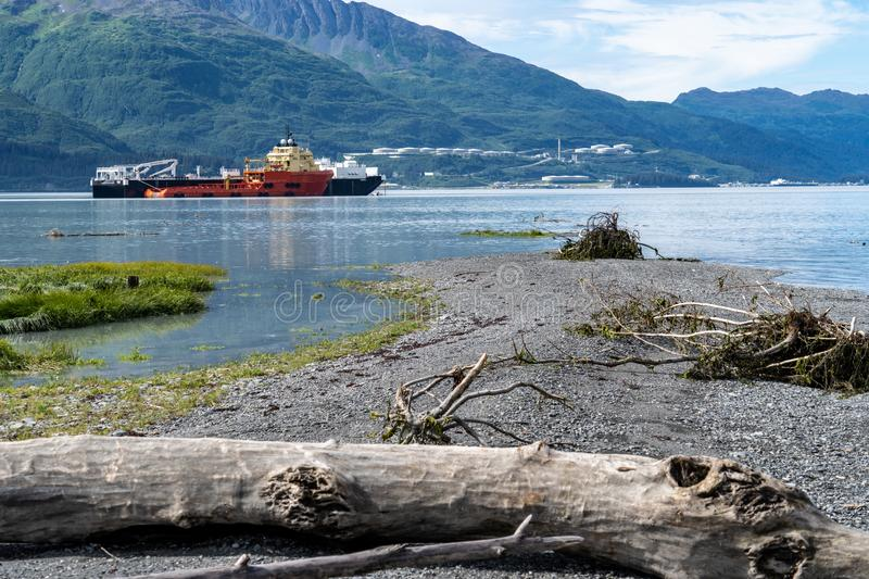 Shoreline of Old Town Valdez Alaska. Log in foreground. Commerical ship in background unidentifiable royalty free stock images