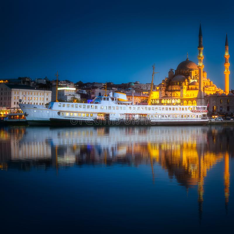 View of public ferry and old district of Istanbul. View of pier, public ferry and old district of Istanbul with Mosque on skyline and reflection on water, Turkey royalty free stock photo