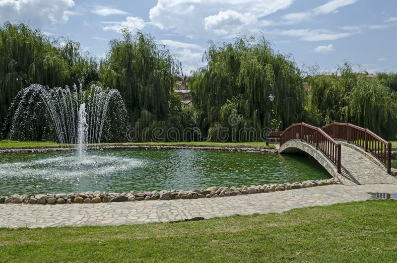 View of public garden with beauty artificial pond, fountain and bridge, town Delchevo among Maleshevo and Osogovo mountains stock photos