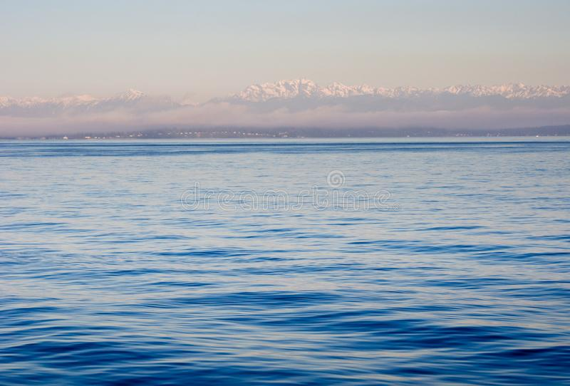 Puget Sound with Olympic Peninsula at sunset. View of Puget Sound with Olympic Peninsula at sunset from water stock photography