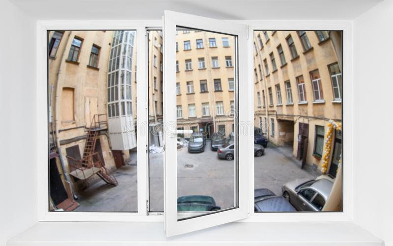View through the pvc window frame on first floor at narrow quadrangle with parked cars. View through the pvc window frame on first floor at the narrow quadrangle royalty free stock photos