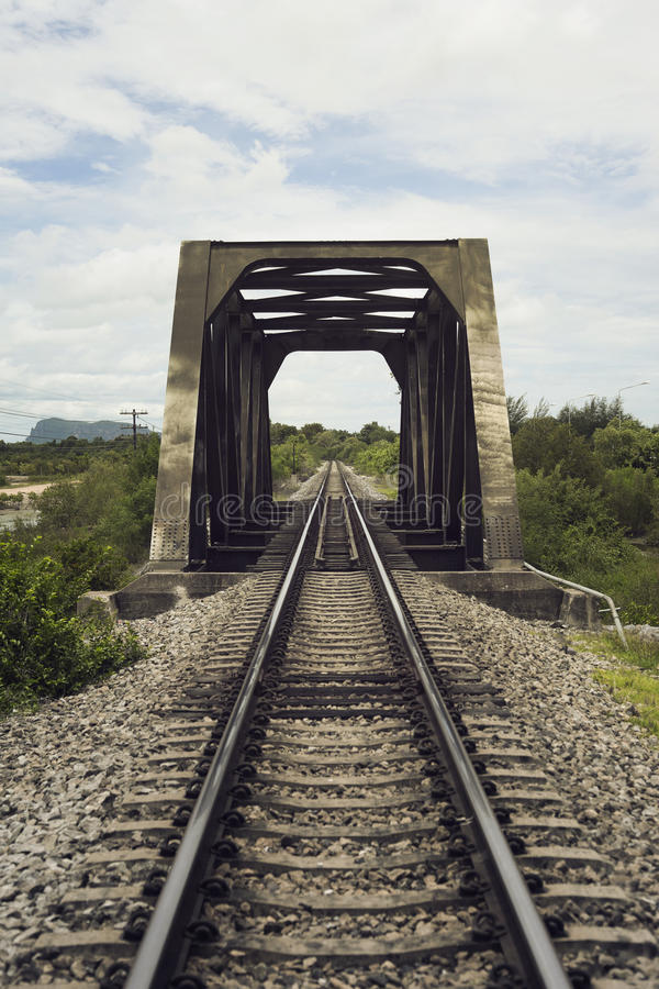 View of railway and old steel bridge with green tree at the left and right side of railway,blue sky and clouds on background stock photography