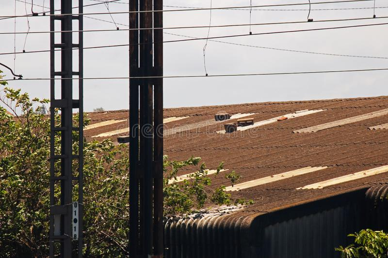 RAILWAY LINE CABLES WITH ROOF OF ABANDONED INDUSTRIAL BUILDING IN THE BACKGROUND stock images