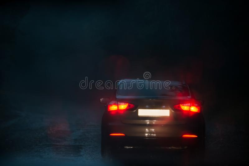 View from a rain-drenched windshield on a car in front. View from a rain-drenched windshield on blurred back lights of a car in front. Heavy rain stock photo