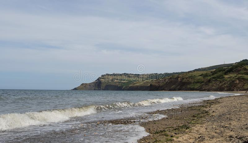 View of Raven Hall, in Ravenscar, from Boggle Hole. Taken on a cooler summer`s day from the beach at Boggle Hole, along the Cleveland Way royalty free stock image