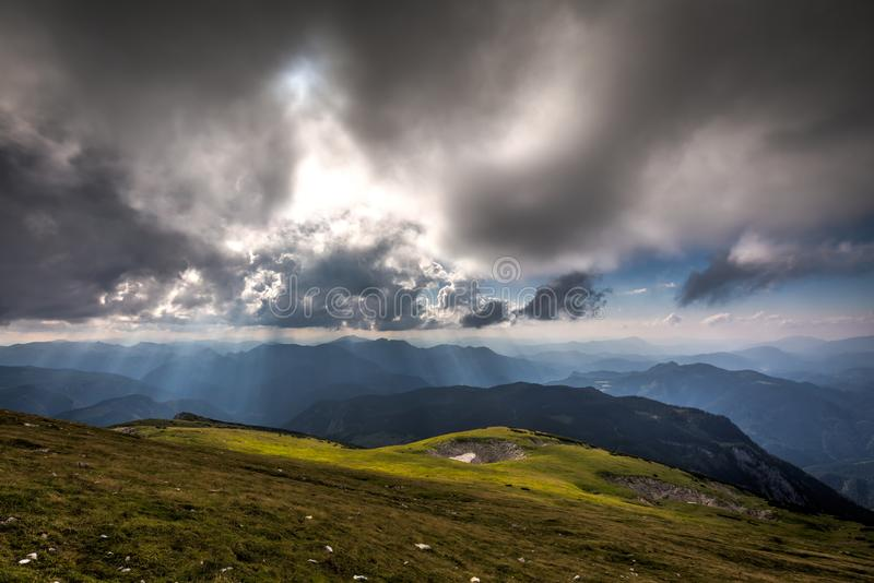 View from Rax plateau, full of fresh, green grassy meadow with blue dramatic cloudy sky to valley and alpine hills royalty free stock images