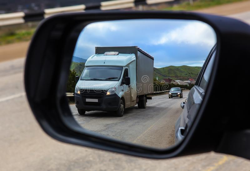 View through the rearview mirror of the car on the movement of cars. On a country highway stock image
